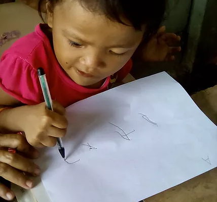 A little girl trying to write on a piece of paper with assistance from an adult