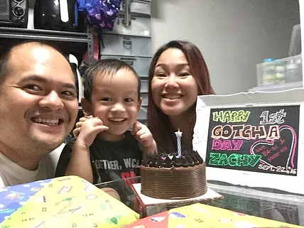 Zachy celebrating his first birthday with his mom and dad