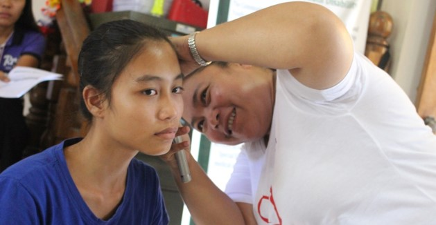 A volunteer conducting an ear screening for a youth with disability