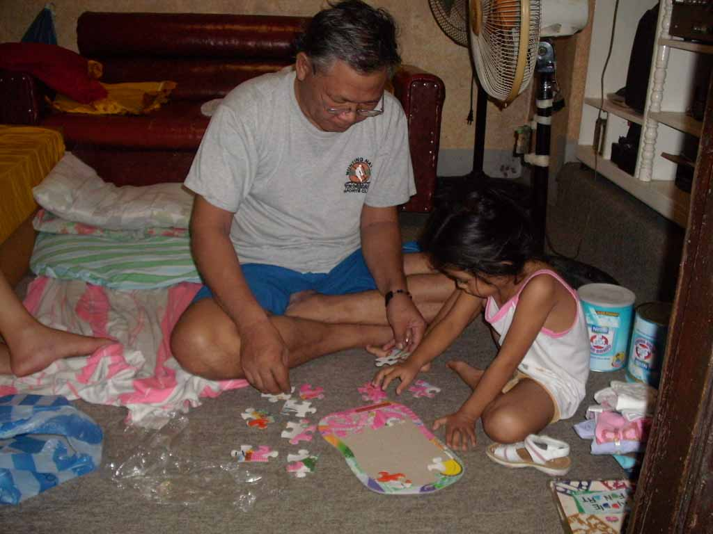 Foster father playing jigsaw puzzle with his daughter