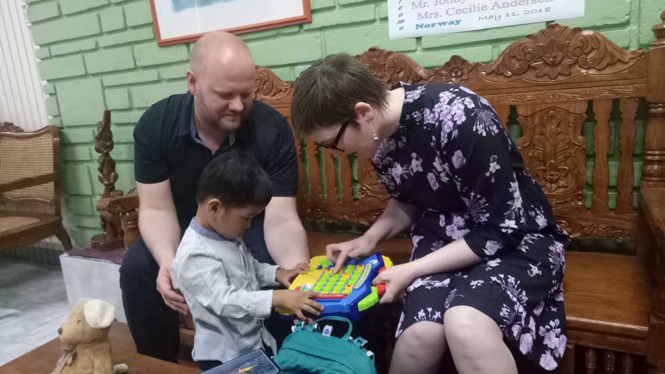 Foreign parents playing with their Philippine-born son
