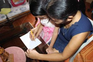 foster mother teaching her daughter how to write