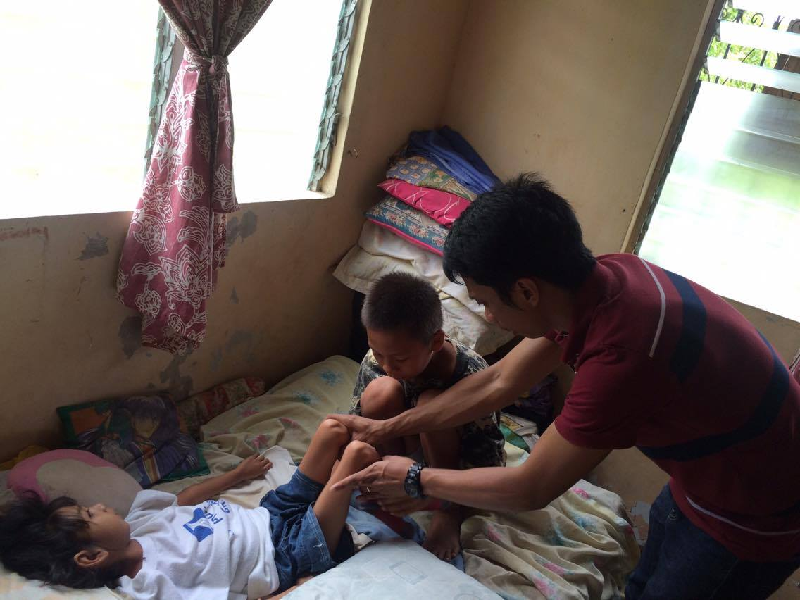 Brother of a child with disability being assisted on doing home therapy for her little sister