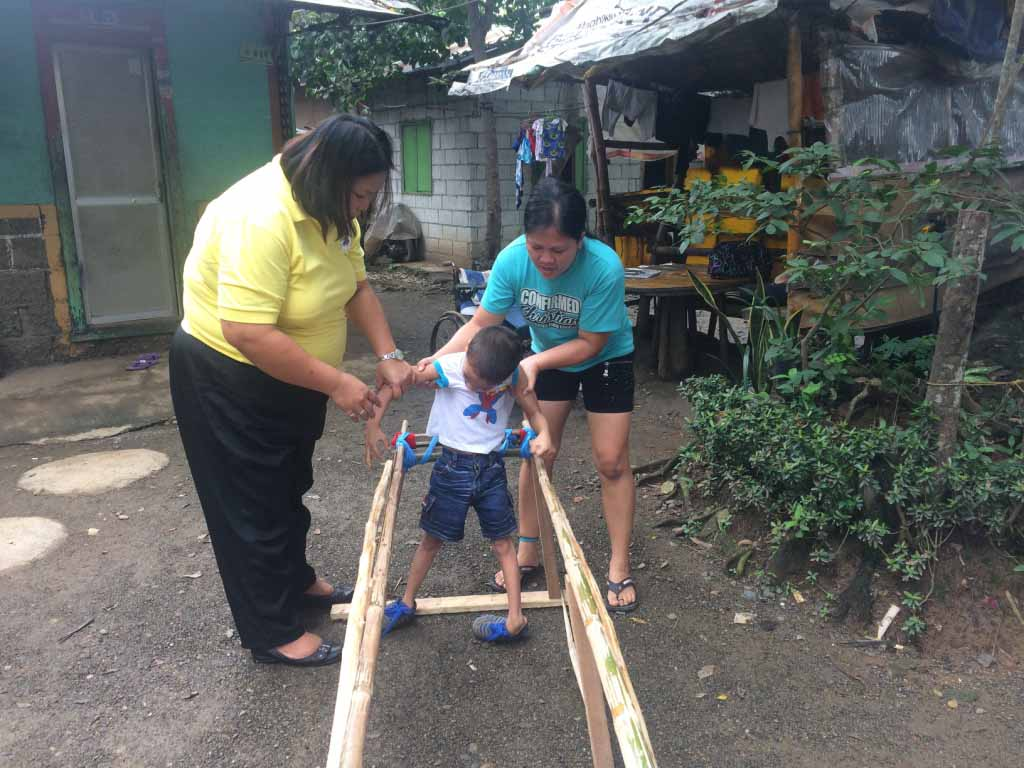 A physical therapist and a mother assisting her son to walk using assistive device