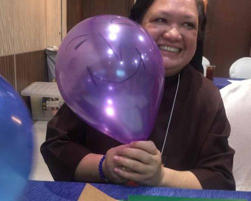 Sister Gudes as one of the participants smiling with a balloon