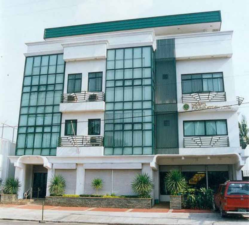 Exterior view of NORFIL Building. Four-story building with parking lot. Painted white and green.
