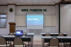Training setup at the NORFIL Training Center with a projector, screen, stage, tables and seats