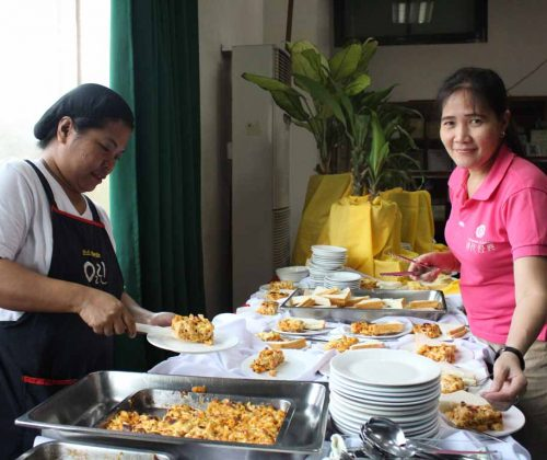 NORFIL staff serving baked macaroni