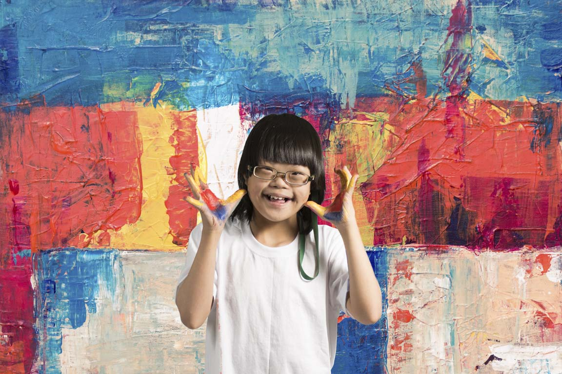A girl with Down syndrome wearing eyeglasses with colorful paint-stained hands