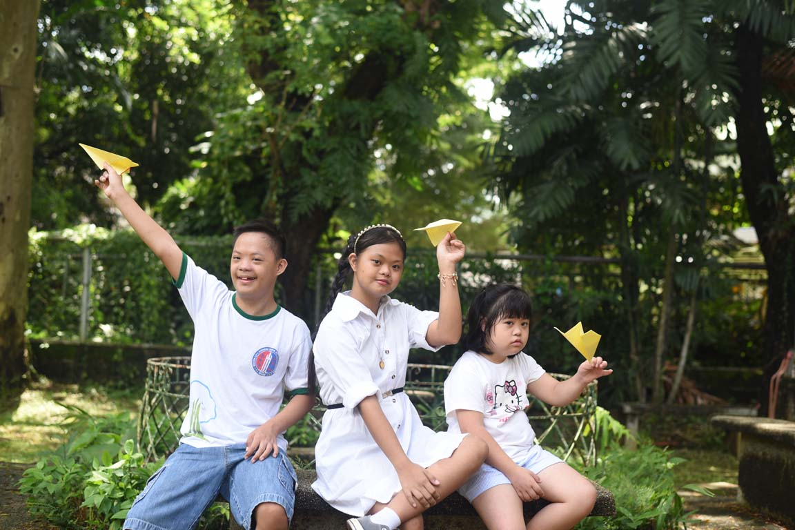 Three children with Down syndrome playing with paper planes at a park